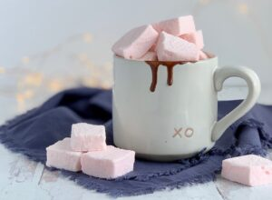 A white mug filled with hot chocolate and topped with homemade fluffy marshmallows