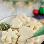 A large plate of Christmas sugar cookies next to a bag of green icing
