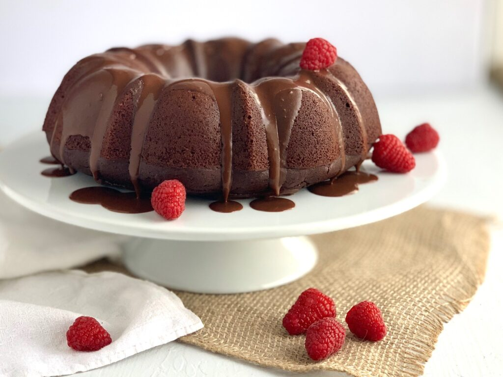 A large chocolate bundt cake on a white serving cake plate with a chocolate ganache running down the sides and random strawberries throughout.