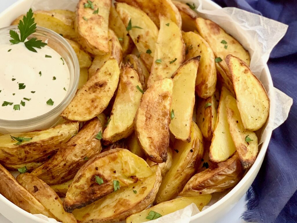 A large serving plate of baked potato wedges with dipping sauce.