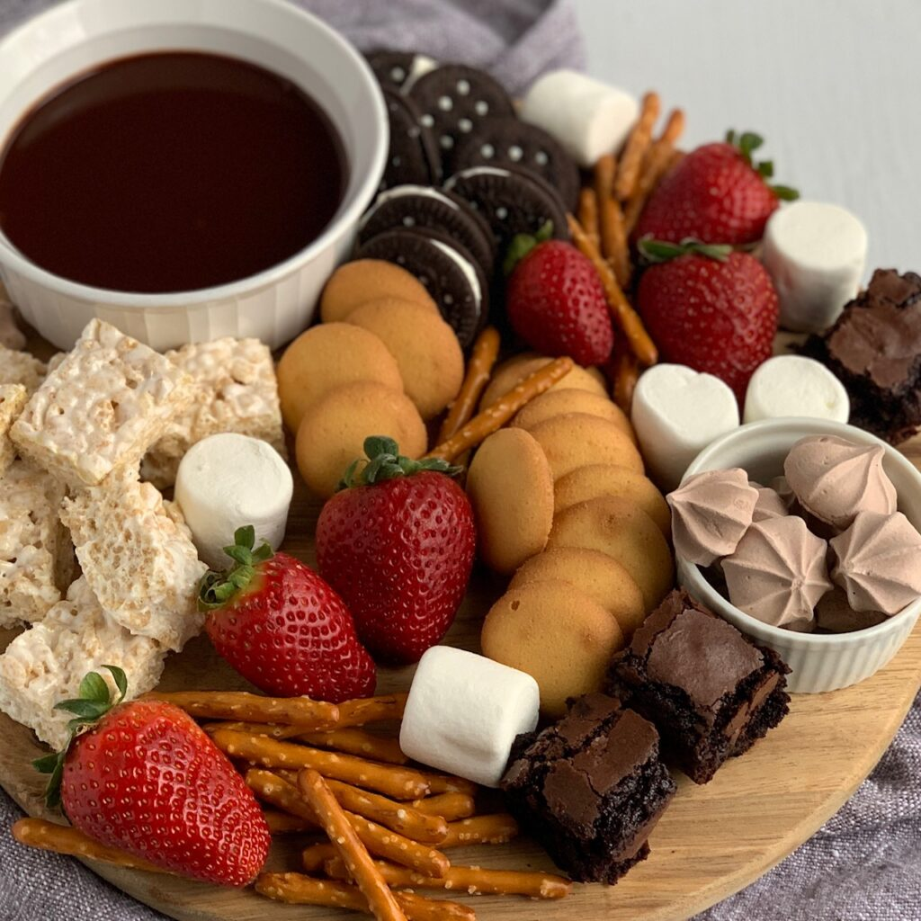 A serving board filled with amzing items such as mini rice krispies, mini brownie bites, safe oreos, pretzels, vanilla wafers, large marshmallows, strawberries and a small bowl of chocolate ganache dipping sauce.