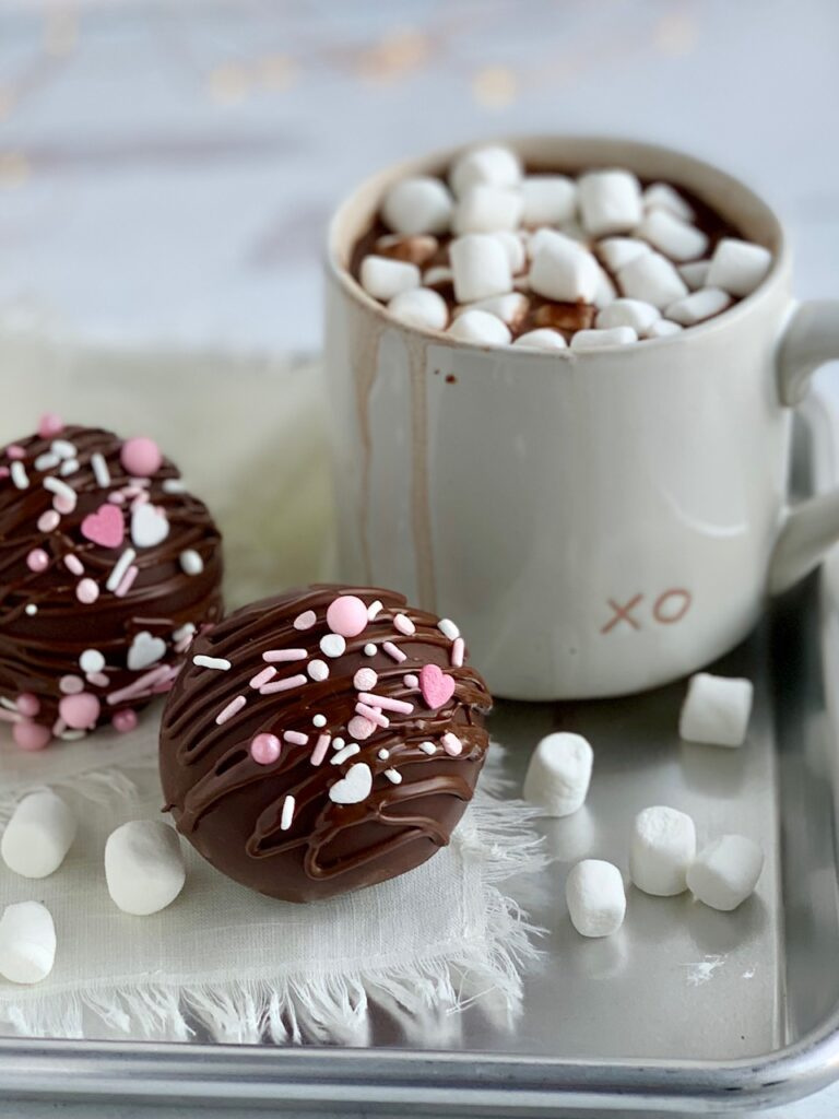 2 hollow chocolate balls filled with hot chocolate mix and sprinkles then decorated with drizzled chocolate on the outside and white and pink sprinkles. All next to a  mug of hot chocolate.