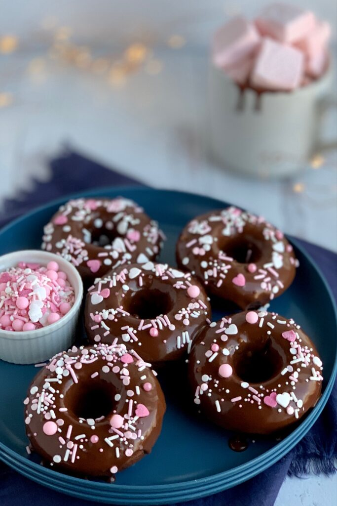 Chocolate Donuts with a chocolate ganache icing topped with white and pink sprinkles on a blue plate.