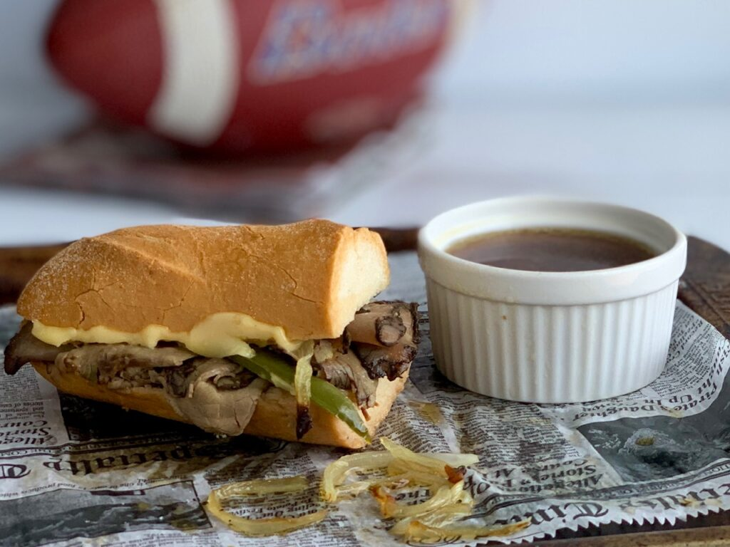 A toasted gluten free baguette with slices of roast beef, onions, and green peppers next to a bowl of au jus.