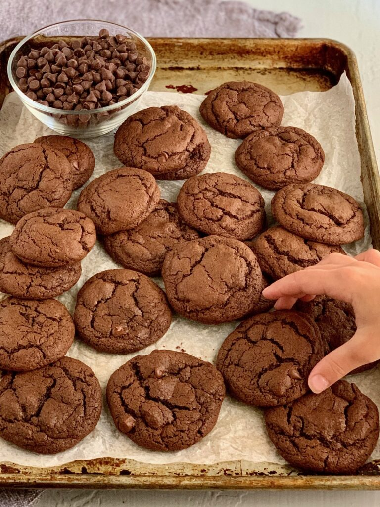 Brownie cookies on a baking sheet with a hand reaching for one.