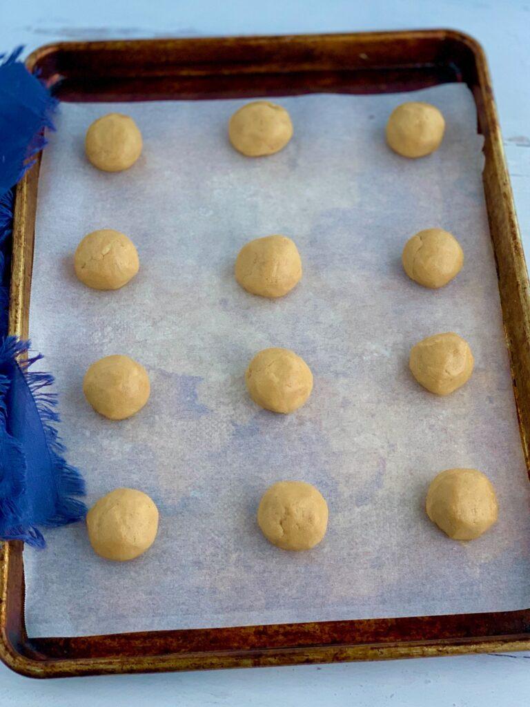 A baking sheet full of round peanut butter balls
