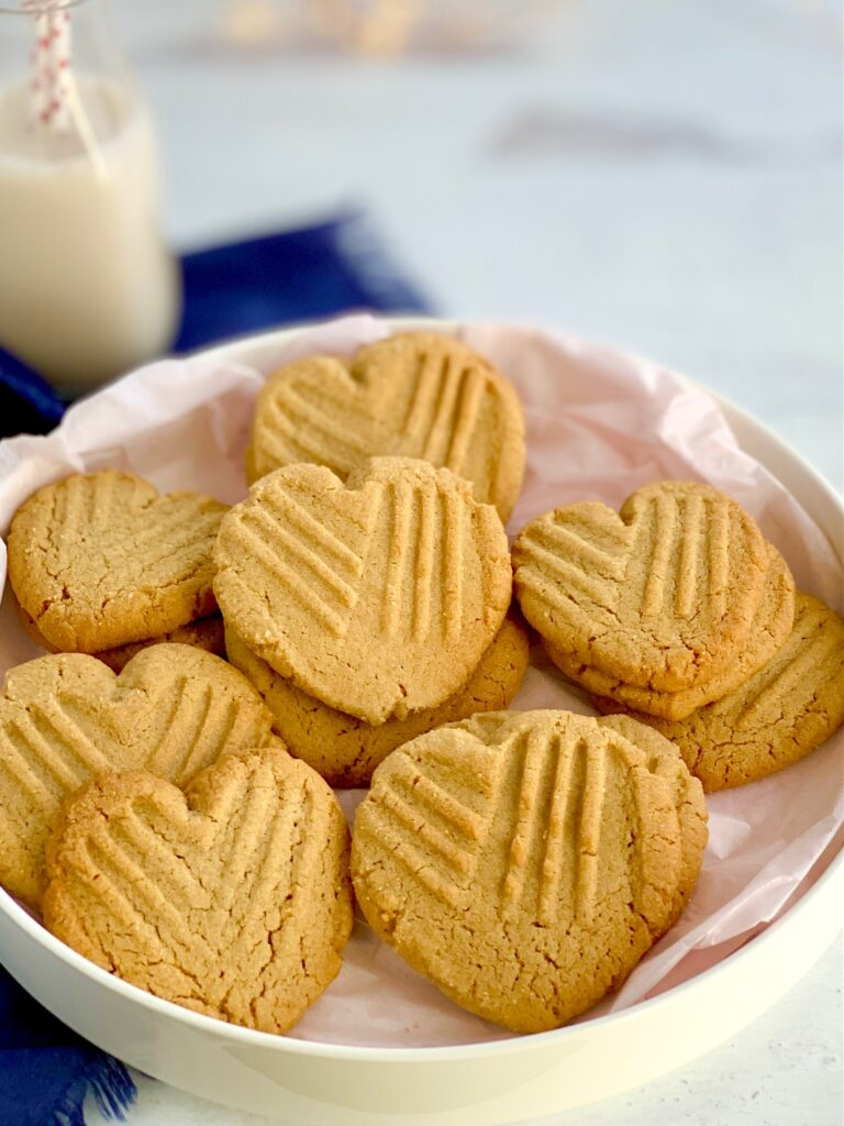 Heart-shaped peanut butter cookies with the classic criss cross pattern on them on a platter.