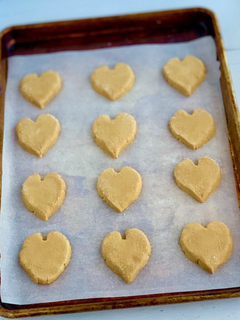 A baking sheet full of raw peanut butter cookies in the shape of a heart.
