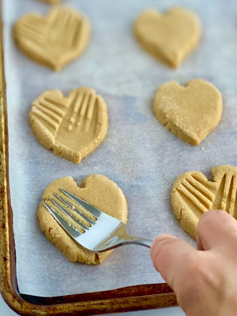 A fork making crisscross patterns in a heart-shaped cookie.