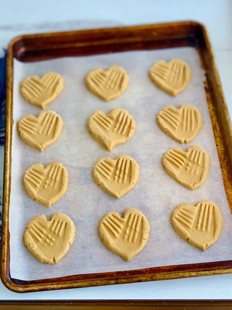 A baking sheet full of heart-shaped cookies with traditional crisscross marks on them.