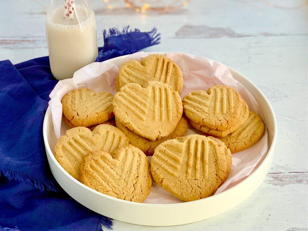 A platter full of heart shaped peanut butter cookies.