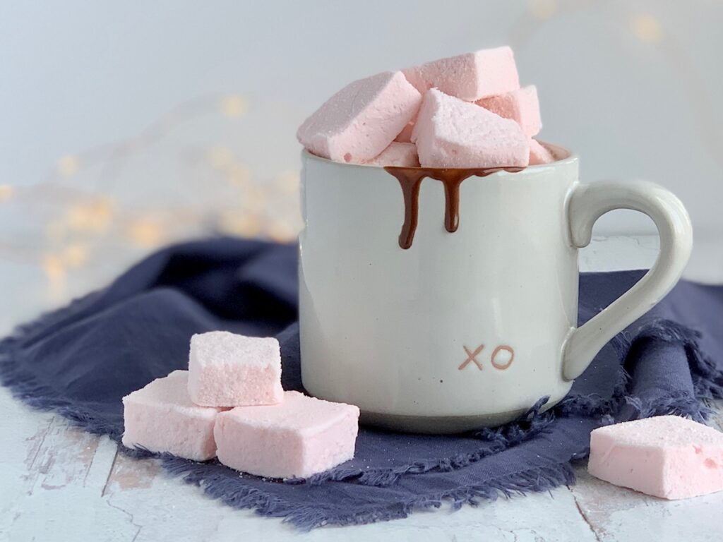 Soft fluffy pale pink square marshmallows on a table next to a mug of hot chocolate.