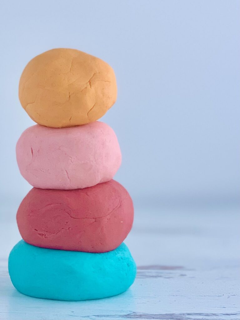 4 balls of playdough stacked on top of each other, blue, dark pink, light pink, and orange.