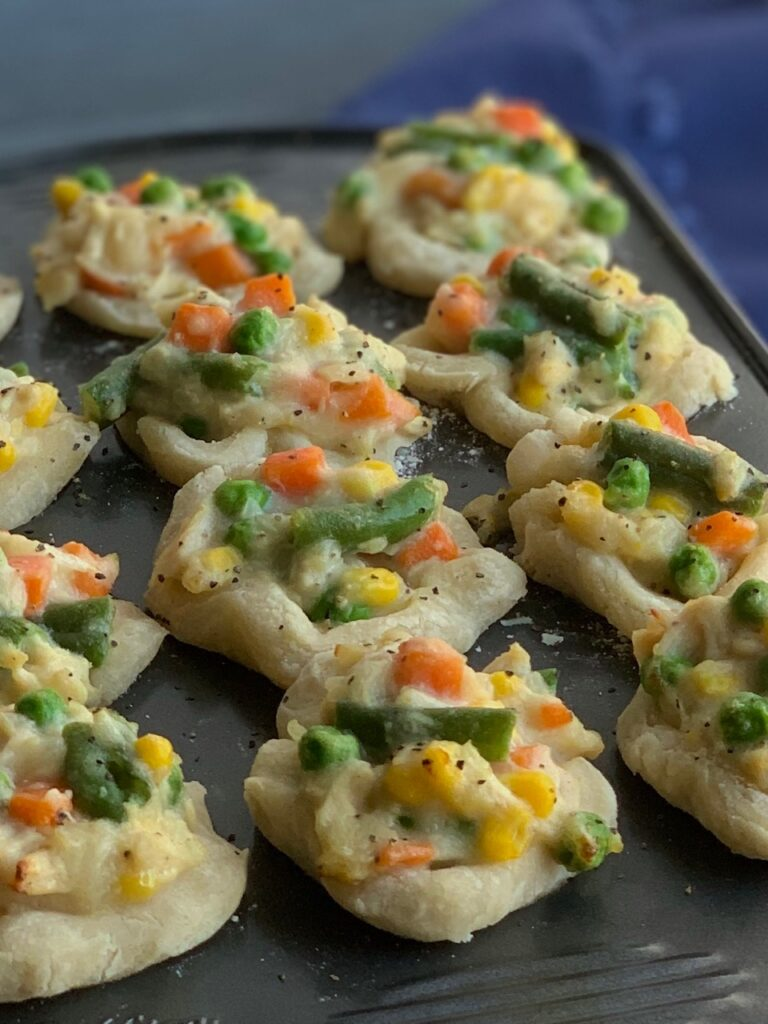 Mini chicken pot pies in a 12 compartment mini muffin pan. Each pot pie is filled with corn, green beans, carrots, and peas.