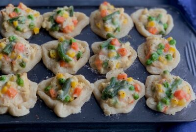 A mini muffin pan filled with a buttery baked crusts in each compartment and then topped with a shredded chicken and veggie filling.