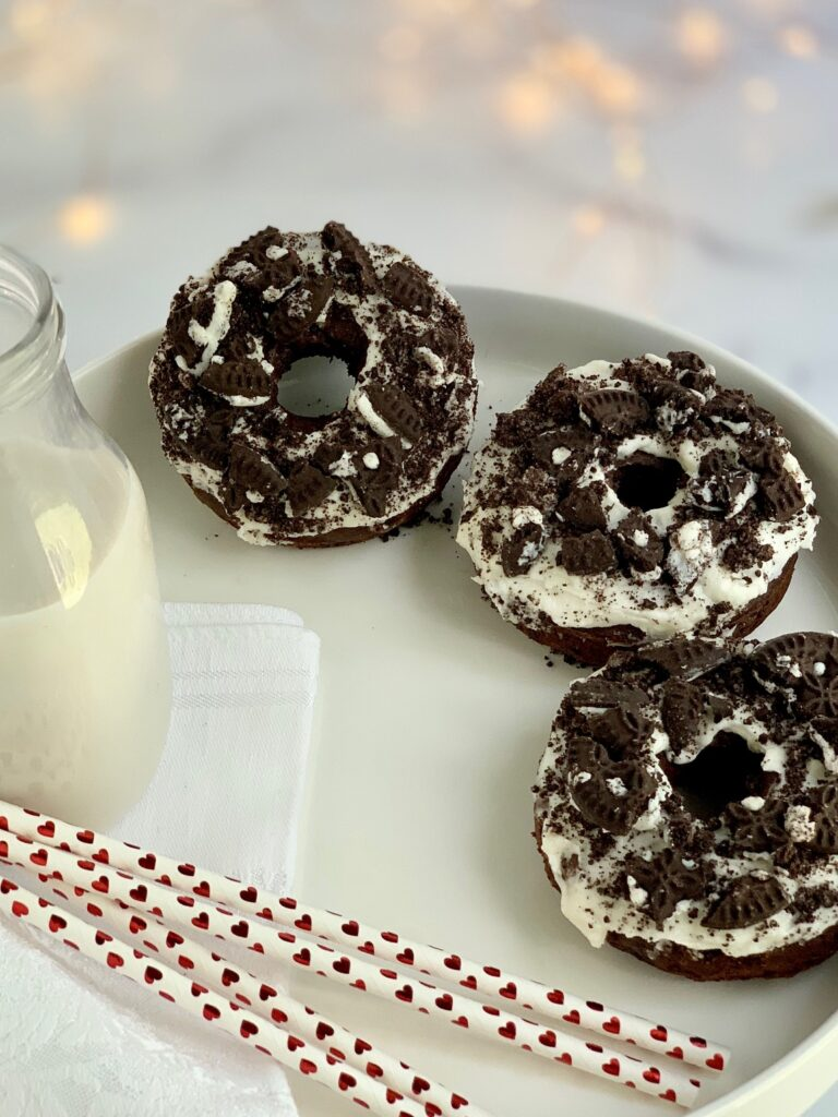 3 oreo donuts with a creamy white frosting and oreo crumbs sprinkled on top next to a glass of milk and 3 straws with red hearts on them.