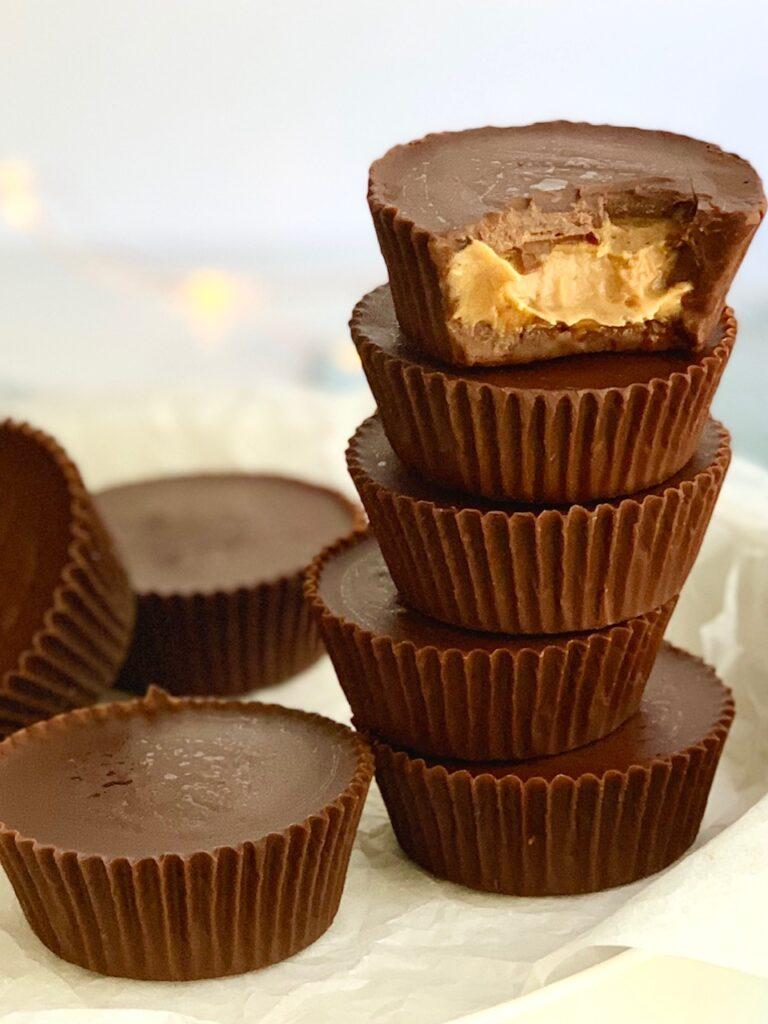 a plate of stacked peanut butter cups and a bite missing out of the top cup. You can see peanut butter.