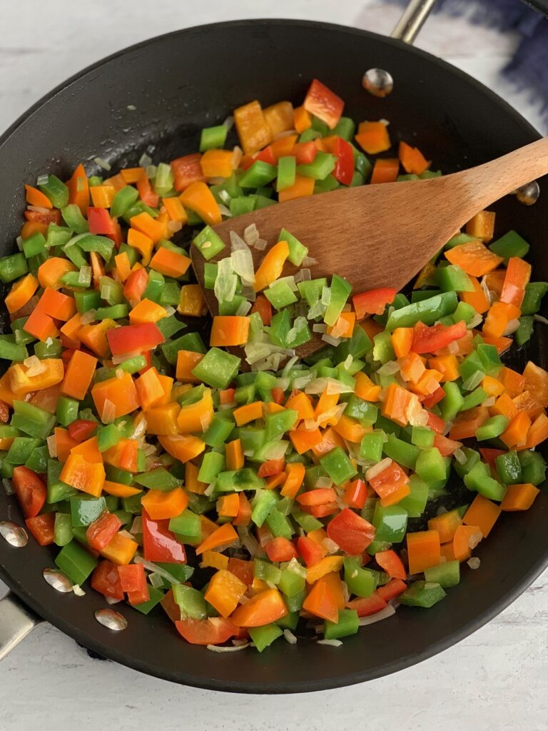 A skillet of sautéing onions, and bell peppers