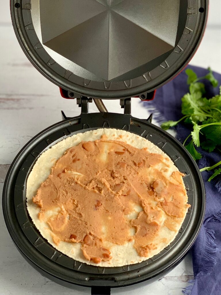 A quesadilla maker with a tortilla and refried beans spread on it.