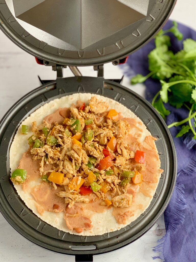 A quesadilla maker with a tortillas on it. On top of the tortillas is refried beans and the shredded chicken and bell pepper mixture.