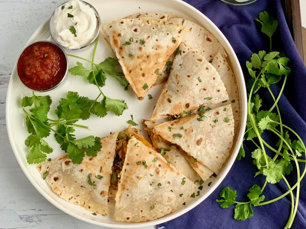 A serving plate of quesadillas cut into triangles and ready to be eaten with a side of dairy free sour cream and salsa.