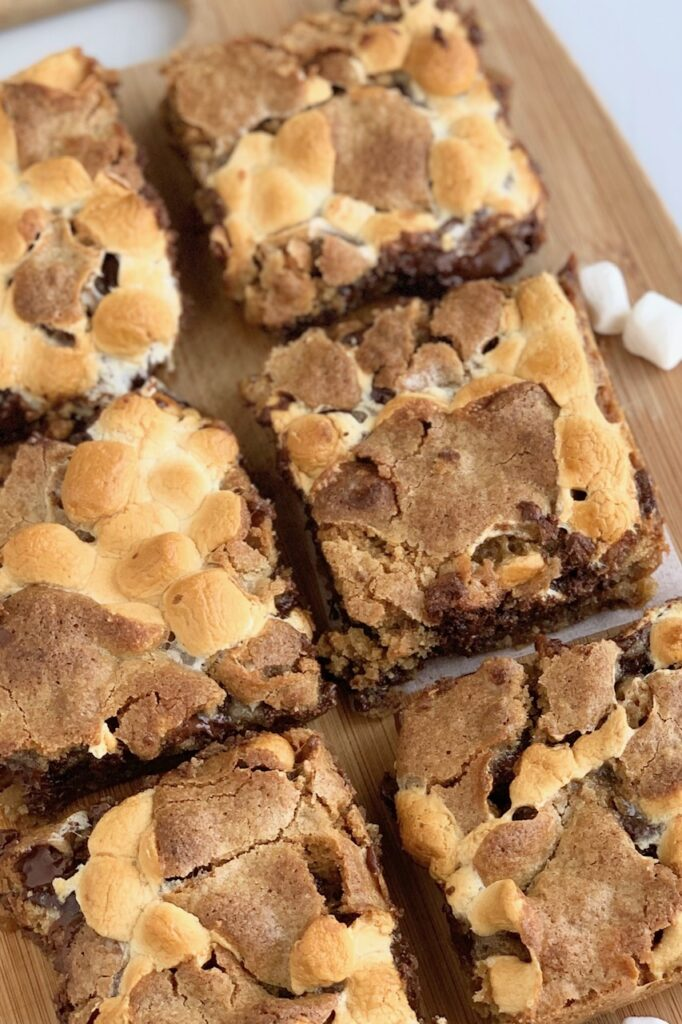 Cut S'more Bars with a graham cracker crust, ooey gooey mini marshmallows, melted chocolate chunks, and a cookie topping.