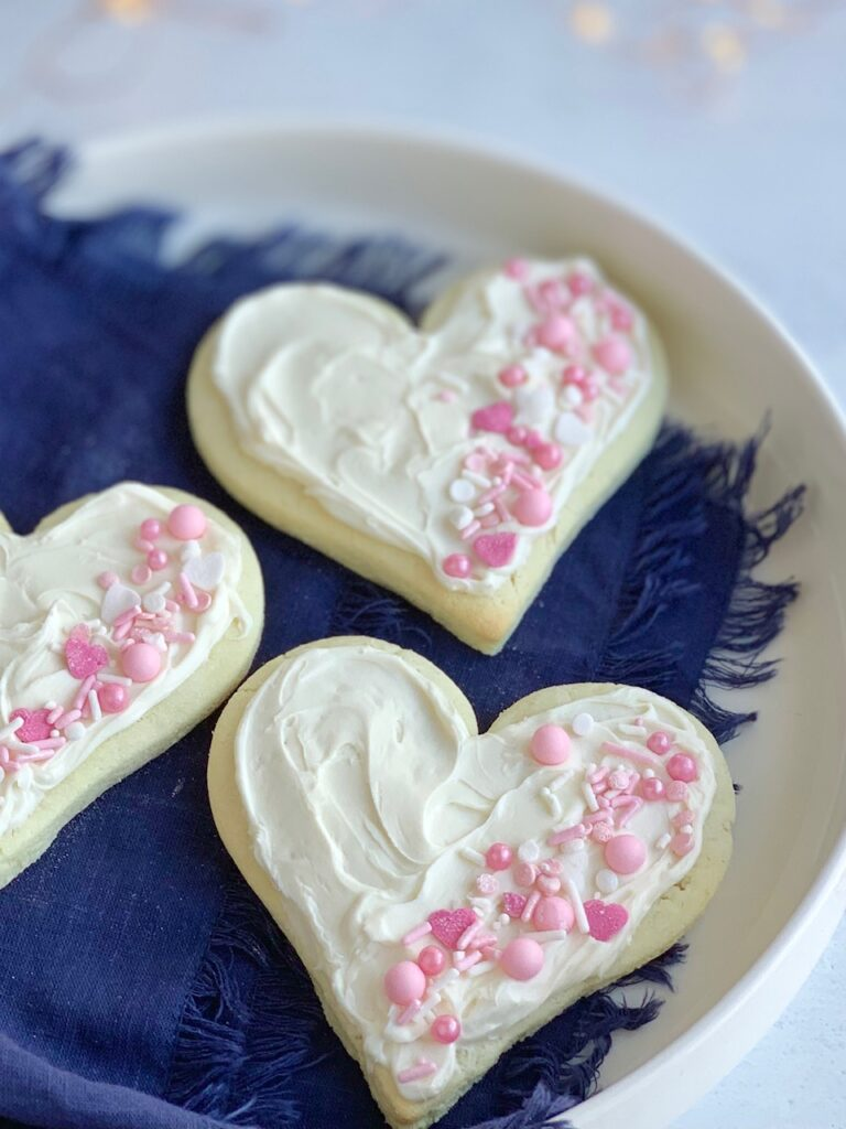 3 heart shaped sugar cookies with white frosting and pink and white sprinkles on the right side of each cookie.