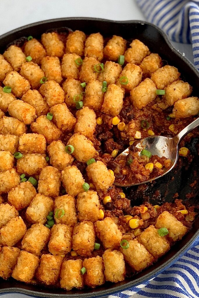 A skillet filled with ground beef, corn, black beans, and taco spices topped with tater tots out of the oven.
