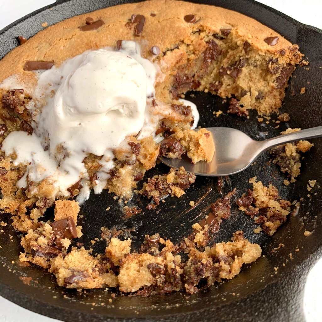 A cast inro skillet filled with a giant baked chocolate chip cookie topped with ice cream.