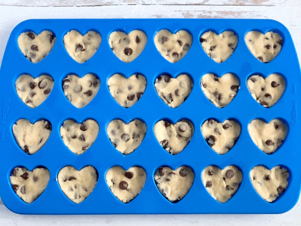 A blue silicone mold that has heart shaped cavities in it. Chocolate chip cookie dough is in the molds.