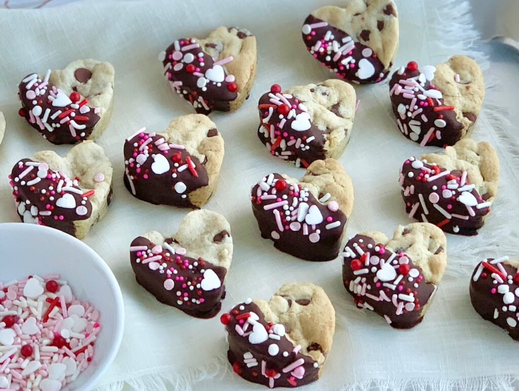 4 rows of mini heart shaped chocolate chip cookies that have been dipped halfway into melted chocolate then topped with pink, white, and red sprinkles.
