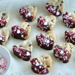 A few rows of heart-shaped chocolate chip cookies that have been dipped in chocolate and topped with sprinkles.