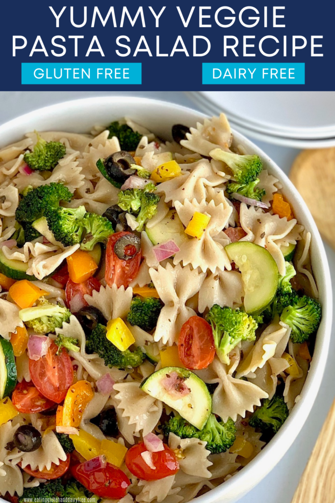 A large white serving bowl of bow tie pasta noodles, diced bell peppers, broccoli, olives, cucumbers, and purple onion with dressing.