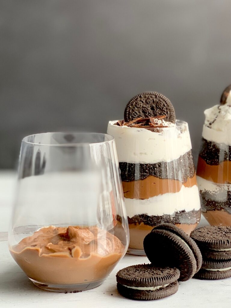 1 glass jar with the first layer of thick chocolate pudding on the bottom next to 2 glass jars layered with a thick homemade chocolate pudding, crushed oreo-like cookies, and a creamy white whipped topping. Then on the very top is more crush cookie, an oreo-like cookie, and chocolate curls. Next to the glass jars are more Oreo-like cookies.