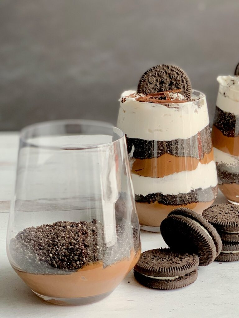 1 glass jar with the first layer of thick chocolate pudding on the bottom and cookie crumbs next to 2 glass jars layered with a thick homemade chocolate pudding, crushed oreo-like cookies, and a creamy white whipped topping. Then on the very top is more crush cookie, an oreo-like cookie, and chocolate curls. Next to the glass jars are more Oreo-like cookies.