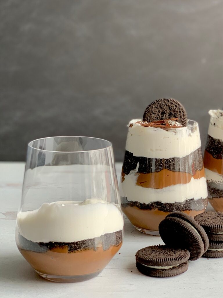 1 glass jar with the first layer of thick chocolate pudding on the bottom, then, cookie crumbs, and whipped topping next to 2 glass jars layered with a thick homemade chocolate pudding, crushed oreo-like cookies, and a creamy white whipped topping. Then on the very top is more crush cookie, an oreo-like cookie, and chocolate curls. Next to the glass jars are more Oreo-like cookies.