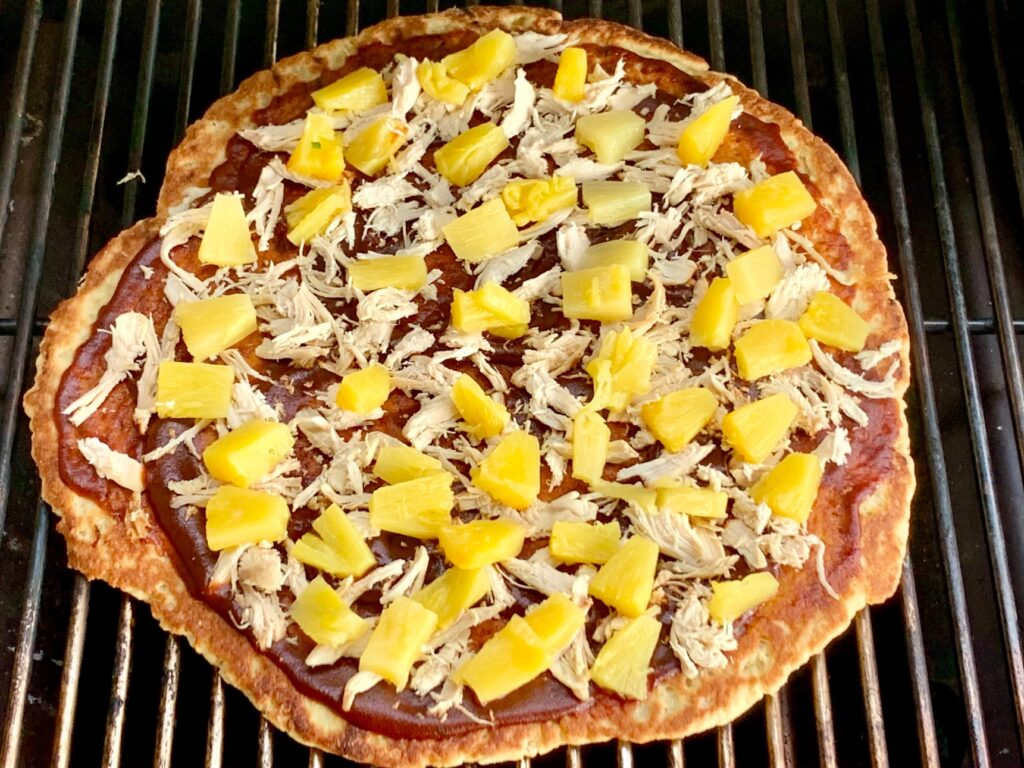 A Hawaiian pizza with BBQ sauce, shredded chicken, and diced pineapple on a grill being cooked.