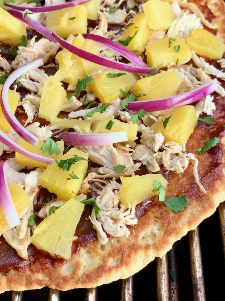 A Hawaiian pizza with BBQ sauce, shredded chicken, purple onions pieces, and diced pineapple on a grill being cooked.