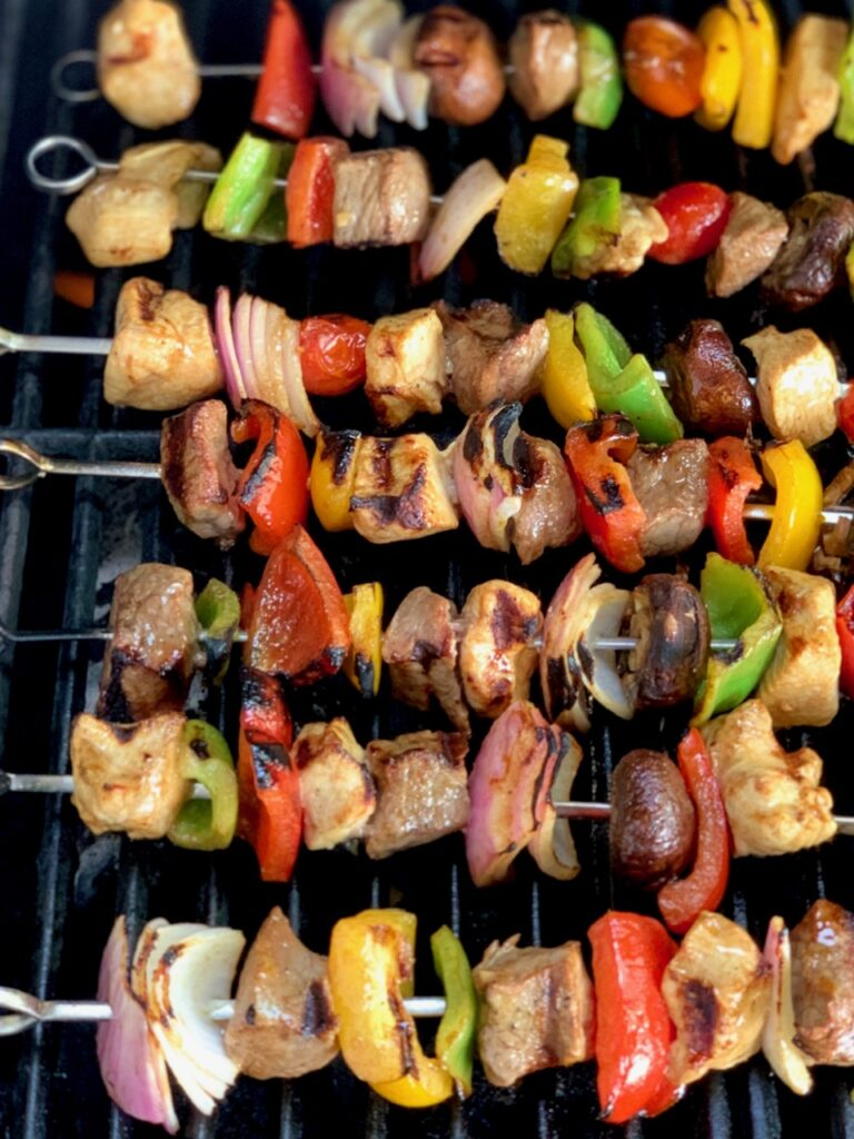 Chicken, steak, onions, and bell peppers on the grill.