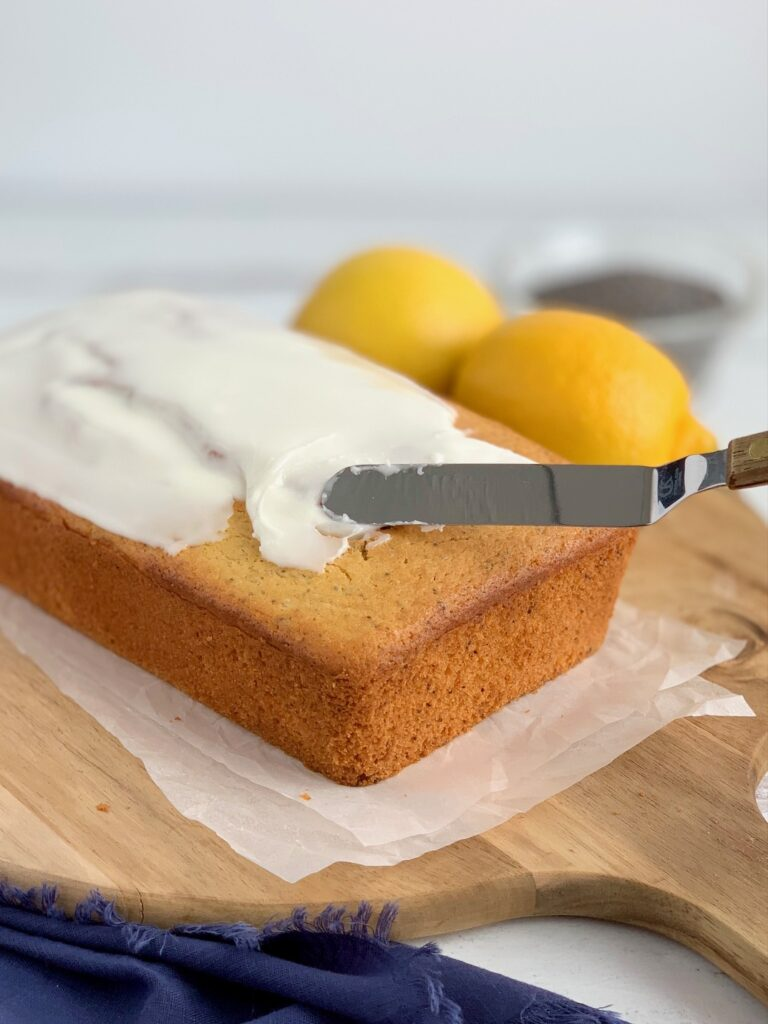Glazing a lemon poppy seed loaf with a powdered sugar and lemon juice icing.
