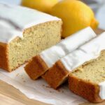 Slices of tender lemon poppy seed bread with a thick icing on top next to two whole lemons.