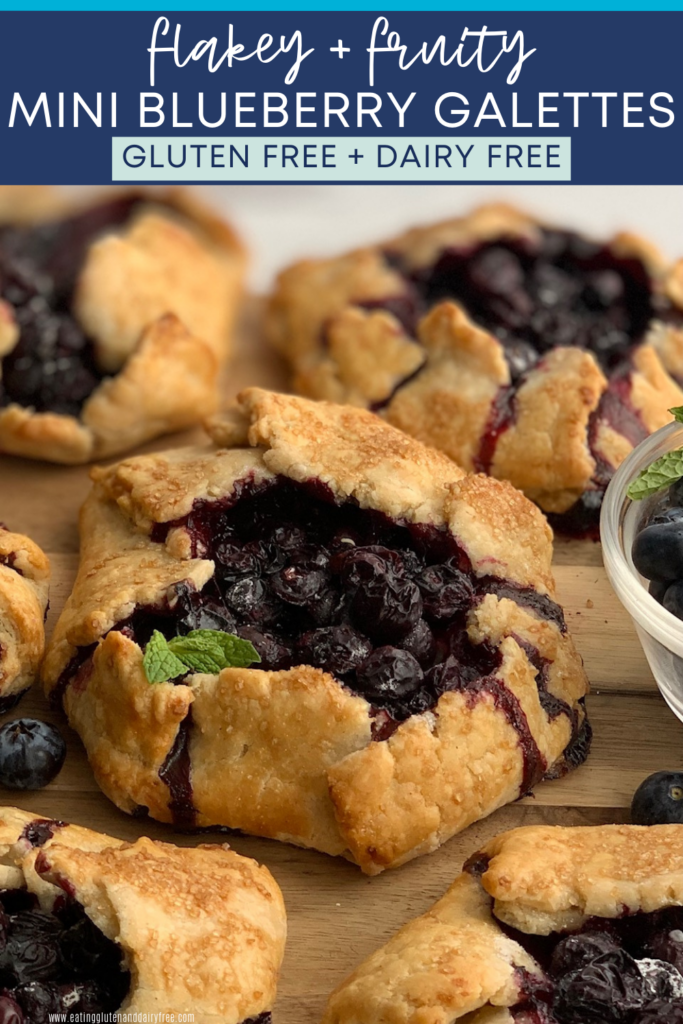 A rustic version of a blueberry pie. A flat pie crust with formed sides to hold a blueberry filling surrounded by more galettes on all sides. On the side is a fresh mint leave.