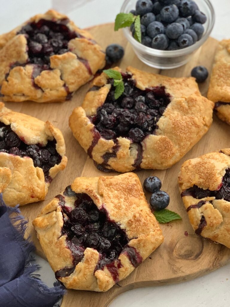 A rustic version of a blueberry pie. A flat pie crust with formed sides to hold a blueberry filling surrounded by more galettes on all sides. On top is a fresh mint leave.