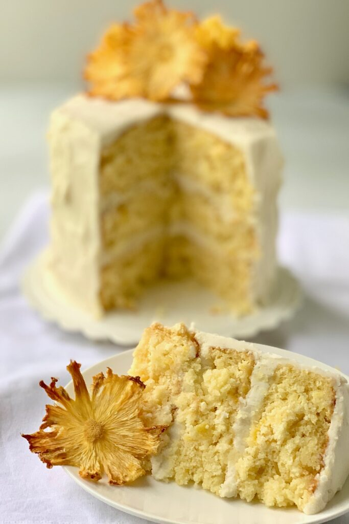 A large slice of cake with small pineapple chunks and  buttercream frosting and a small 3 tired cake behind it with dried pineapple rings on it.