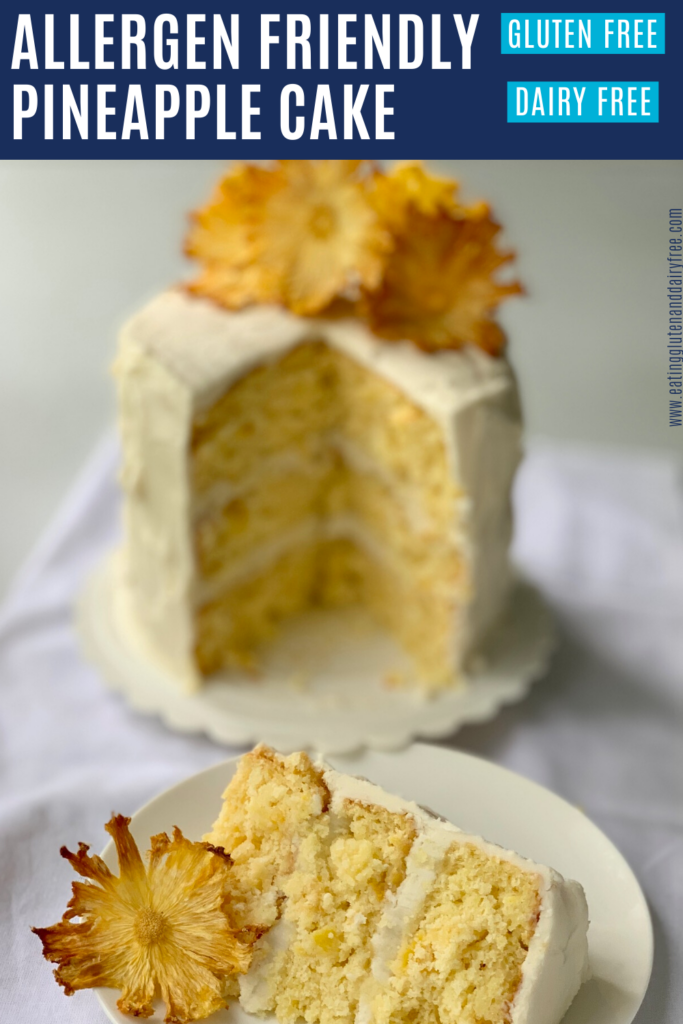 A 3 layer vanilla pineapple cake with buttercream frosting. The cake is topped with fried pineapple rings. In front of the cake is a slice of the cake on a plate.