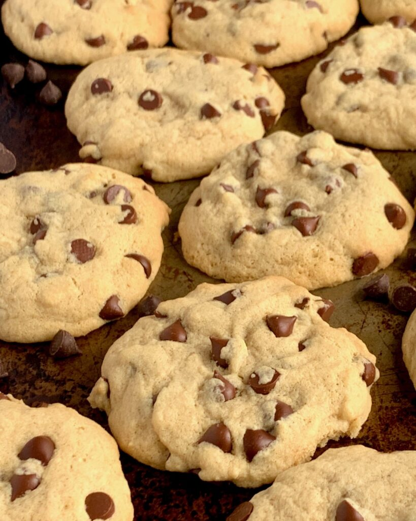 Baked chocolate chip cookies on a cookie sheet.