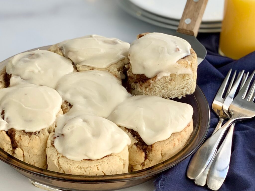 A round pie pan filled with  gooey soft cinnamon rolls with a cream cheese frosting.