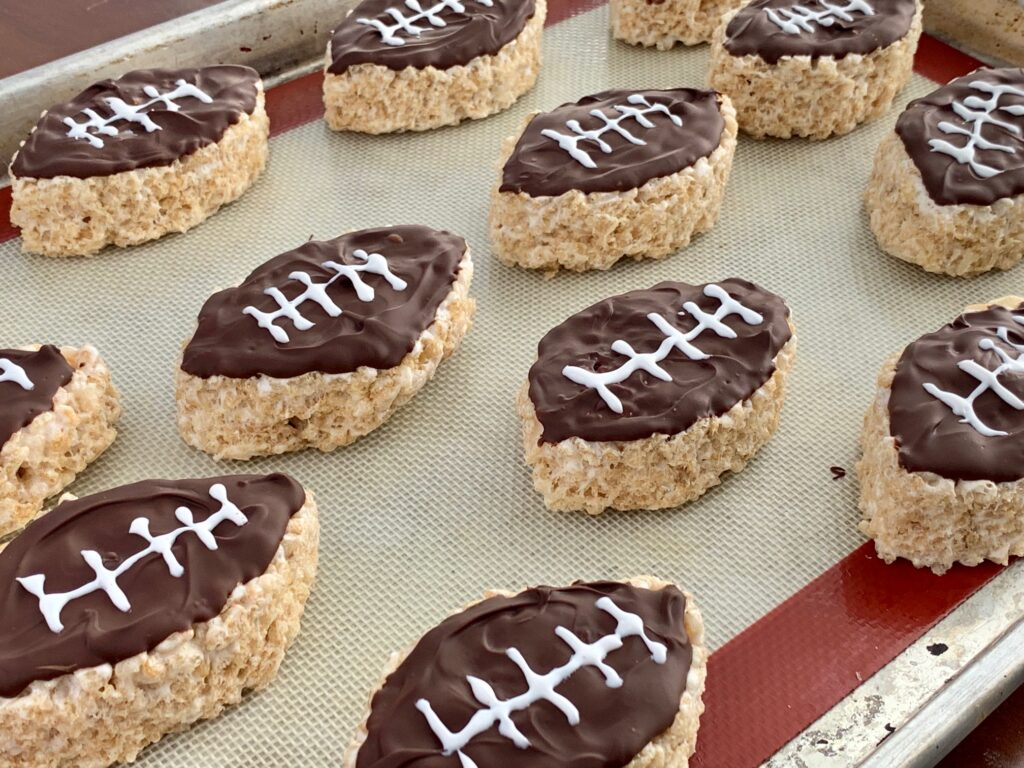 Rice krispie in the shape of a football with melted chocolate on top and white icing to looking like a football.