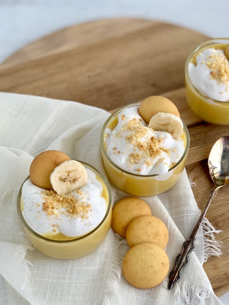 The top view looking down of 3 mini dessert glasses filled with layers of sliced bananas, vanilla wafer cookies, banana pudding, and creamy whipped topping. Then cookie crumbs, another cookie, and a banana slice on top of that.