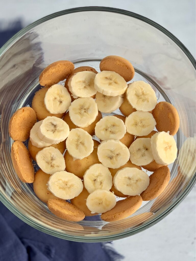 A glass trifle bowl filled with layers of vanilla wafer cookies and sliced bananas.